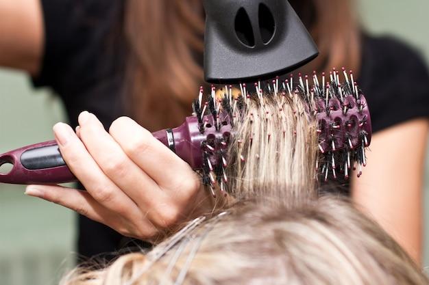 Le coiffeur sèche les cheveux dans un salon de beauté