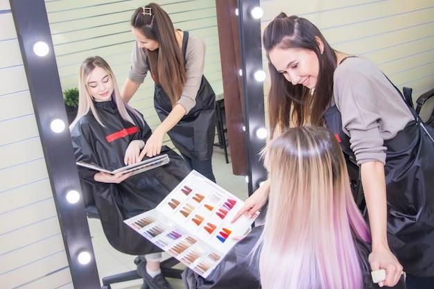Le coiffeur sélectionne la couleur des cheveux pour le client de la fille