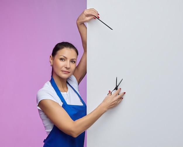 Coiffeur styliste d'apparence asiatique pose avec un panneau d'affichage blanc. concept publicitaire