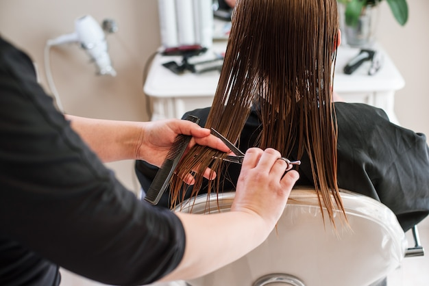 Coiffeur styliste faisant la coupe de cheveux gros plan de l'équipement de travail