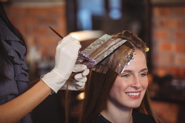 Coiffeur teignant les cheveux de son client