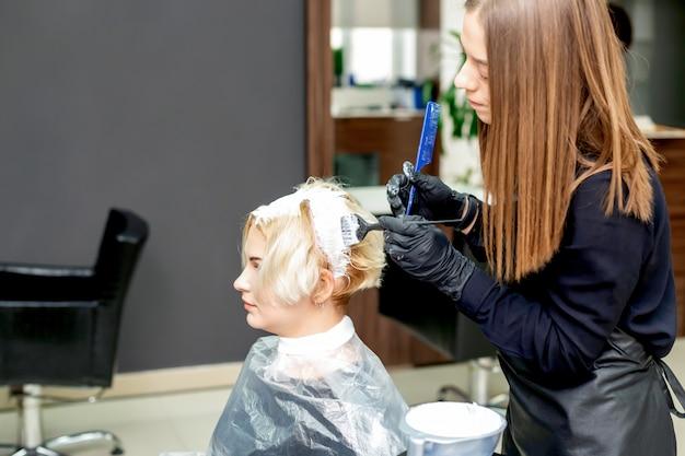 Le coiffeur teint les cheveux de la femme.