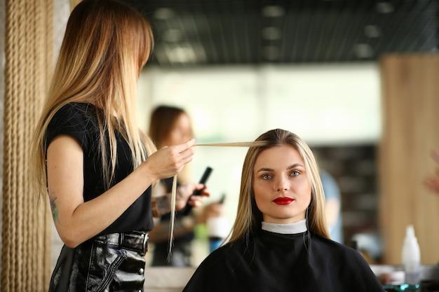 Coiffeur tenant une mèche de cheveux longs du client