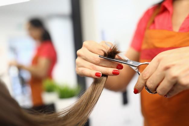 Le coiffeur tient des ciseaux et des pointes de cheveux dans ses mains