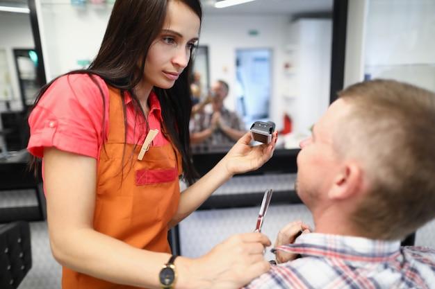 Le coiffeur tient la tondeuse à cheveux dans ses mains et communique avec le client.