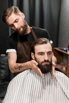 Coiffeur toilettant la barbe de l'homme dans le salon de coiffure