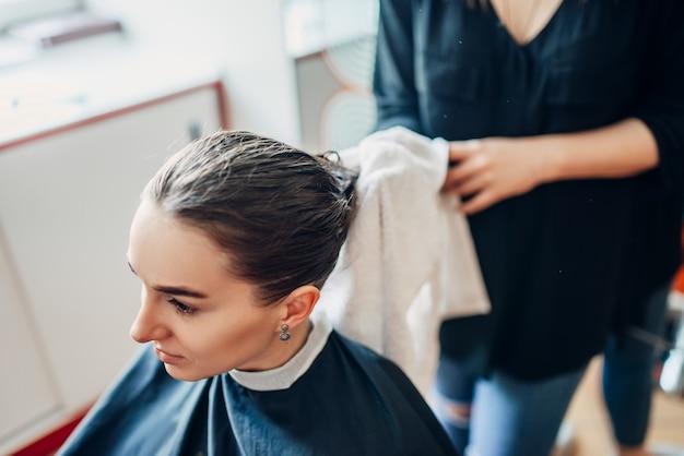 Le coiffeur travaille avec de la laque pour cheveux, une cliente dans un salon de coiffure. fabrication de coiffure dans un salon de beauté