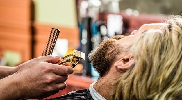 Le coiffeur travaille avec une tondeuse à barbe. client hipster se coupe les cheveux. mains d'un coiffeur avec une tondeuse à barbe, gros plan. homme barbu en salon de coiffure. homme visitant un coiffeur dans un salon de coiffure.