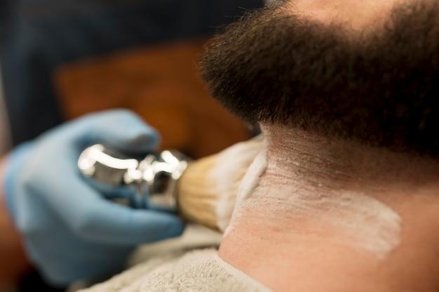 Coiffeur utilisant de la crème à raser pour contourner la barbe du client masculin