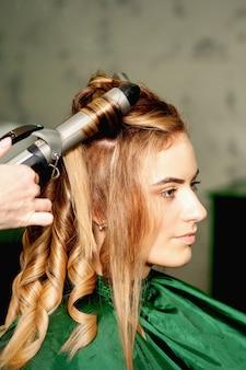 Le coiffeur utilisant des pinces à friser boucle de longs cheveux bruns sur la jeune fille caucasienne dans un salon de beauté