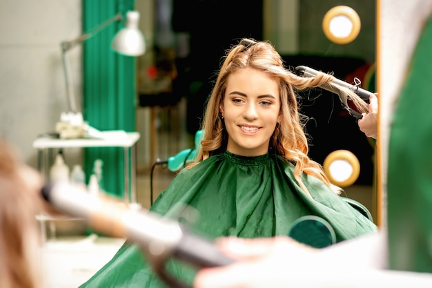 Le coiffeur utilisant des pinces à friser boucle de longs cheveux bruns sur la jeune fille caucasienne dans un salon de beauté.