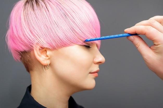 Coiffeur vérifiant la coiffure rose de la femme.