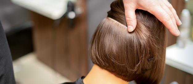 Coiffeur vérifie la coiffure brune courte d'une jeune femme dans un salon de beauté
