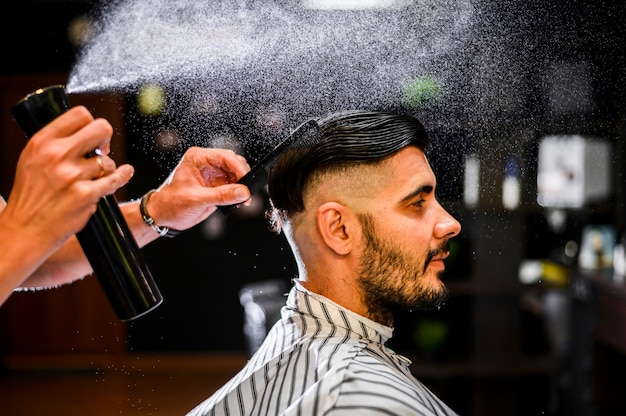 Coiffeur vue de côté pulvériser les cheveux de son client
