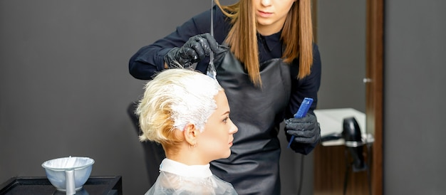 Coiffeurs teinture cheveux de jeune femme de race blanche dans un salon de coiffure