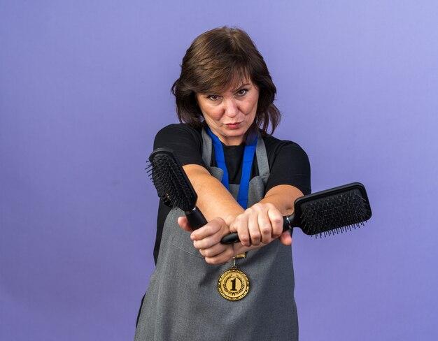 Coiffeuse adulte confiante en uniforme avec une médaille d'or autour du cou tenant des peignes isolés sur un mur violet avec espace de copie