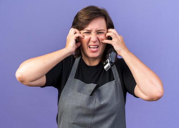 Coiffeuse caucasienne adulte mécontente en uniforme se grattant le visage avec les mains tenant une tondeuse à cheveux isolée sur un mur violet avec espace de copie