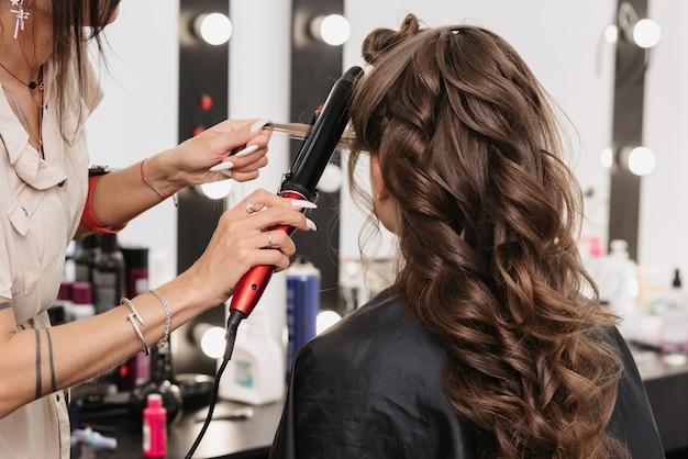 Une coiffeuse fait la coiffure de la mariée