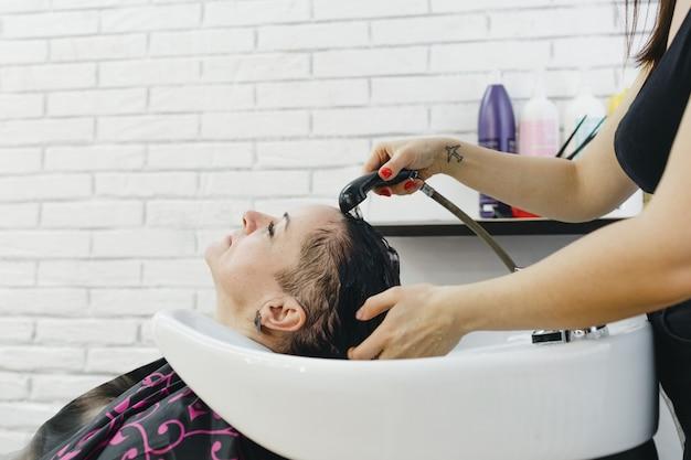 La coiffeuse lave doucement les cheveux du client dans le salon de beauté.