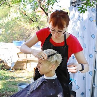 Coiffeuse professionnelle de jeune femme, fait la coupe de cheveux à sa famille dans la cour