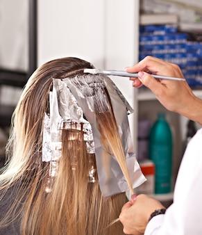 Coiffeuse professionnelle teinture des cheveux de son client.