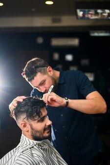 Une coiffeuse qui donne au client une nouvelle coupe de cheveux