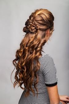 Coiffure boucles ondulées. coiffure sur femme cheveux roux roux aux cheveux longs sur fond gris. services de coiffure professionnels.coiffure, fabrication de tresses avec épingle à cheveux.