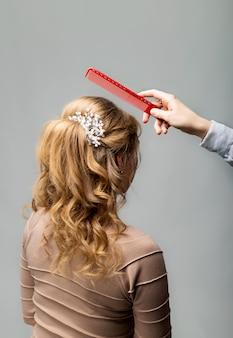 Coiffure boucles ondulées. salon de coiffure faisant la coiffure aux cheveux blonds femme aux cheveux longs à l'aide d'un peigne sur fond gris. services de coiffure professionnels processus de coiffure, fabrication de tresses avec épingle à cheveux