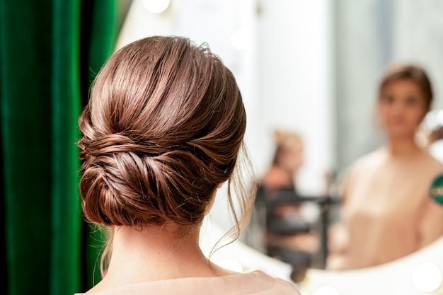 Coiffure de jolie jeune femme brune devant le miroir vue arrière au salon de beauté.