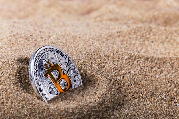 Coin bitcoin enfoui dans le sable.