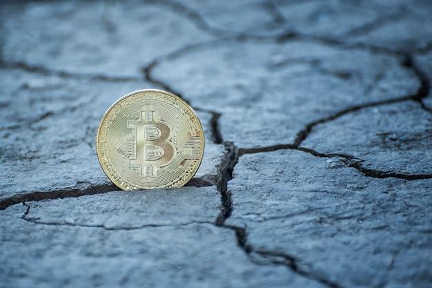 Coin bitcoin sur un sol fissuré. concept financier