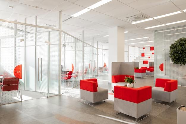 Coin de bureau moderne avec murs blancs, sol gris, espace ouvert avec fauteuils rouges et blancs et pièces derrière un mur de verre