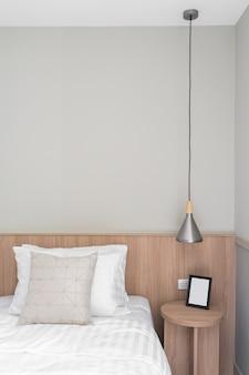 Coin chambre avec cadre en bois noir sur table d'appoint en bois de style scandinave moderne