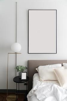 Coin chambre confortable avec tête de lit en tissu marron moderne et réglage d'oreillers confortables avec lampe en or et plante artificielle dans un vase en verre sur une table d'appoint