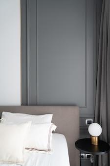 Coin de chambre à coucher décoré de moulures peintes par pulvérisation gris classique de style classique moderne avec lampe de table en or sur une table d'appoint en bois noir