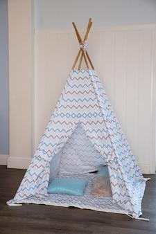Coin chambre d'enfant avec une tente de tipi de jeu joliment décorée et des oreillers.tente de jeu confortable pour les enfants comme élément de l'intérieur de la pépinière.enfants wigwam.décorative cabane confortable de style boho avec décor.