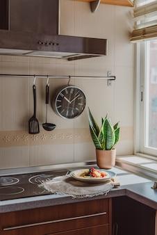 Coin comptoir de cuisine avec une horloge noire, une plante et un ustensiles de cuisine en bois et des crêpes aux baies et bananes sur une assiette