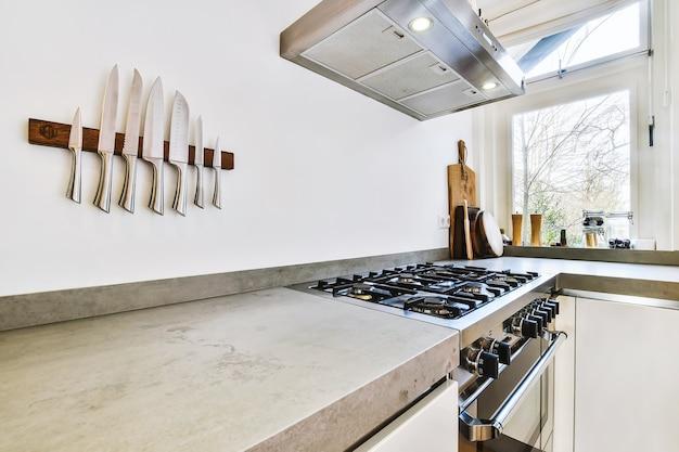 Coin cuisine contemporain avec comptoir en pierre grise et cuisinière à gaz sous hotte chromée au mur avec couteaux inox sur support magnétique