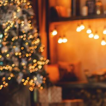 Coin lecture près de la cheminée et arbre de noël avec des cadeaux. flou.