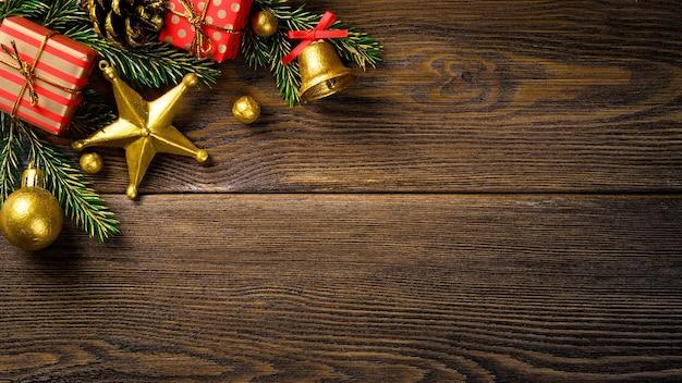 Coin de noël avec des branches de sapin cône de pin jingle bell et coffrets cadeaux rouges sur planche rustique marron.