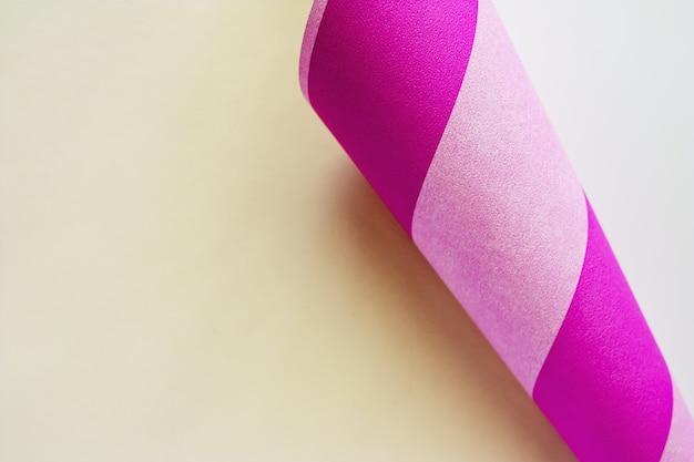 Coin de papier courbé texturé avec côté rayé rose pour le fond