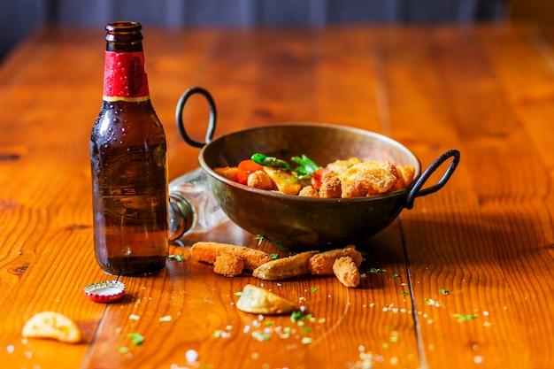 Coin de pommes de terre frites et pépites de poulet dans l'ustensile de cuivre sur la table en bois