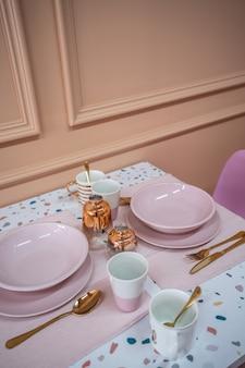 Coin repas avec table en terrazzo et chaise bébé rose