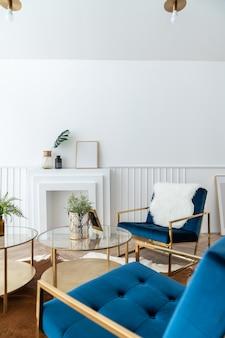 Coin salon confortable avec fauteuil en tissu velours doré et bleu et table basse miroir dorée dans un style classique moderne avec scène de lumière naturelle