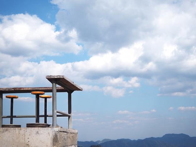 Coin des tabourets et des tables en plein air contre le ciel bleu avec vue de nuage blanc.