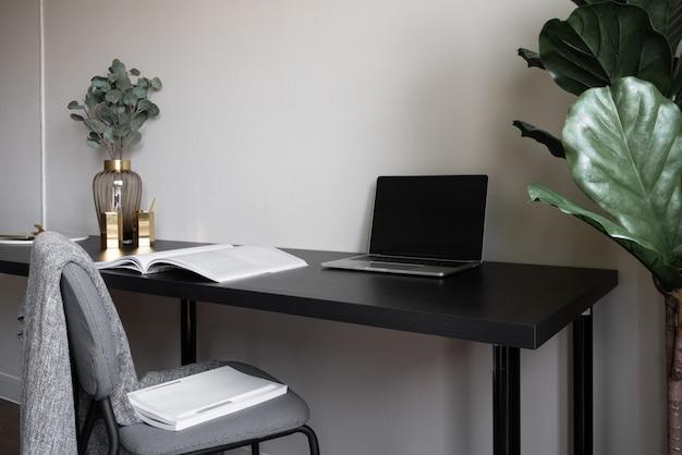 Coin de travail de la chambre décoré de bougies blanches pour ordinateur portable et de plantes artificielles dans un vase en verre sur une table de travail en bois avec fond de mur peint beige