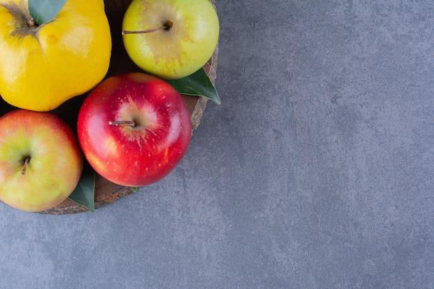 Coing et pommes à bord sur la surface sombre