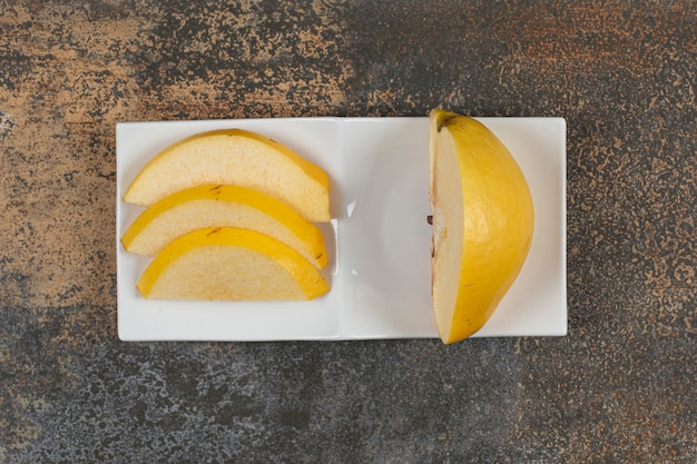 Coing tranché mûr sur plaque carrée blanche