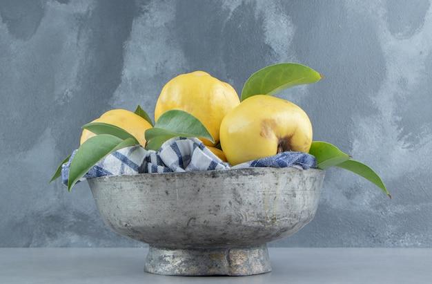 Coings et feuilles empilées dans un bol en métal sur marbre
