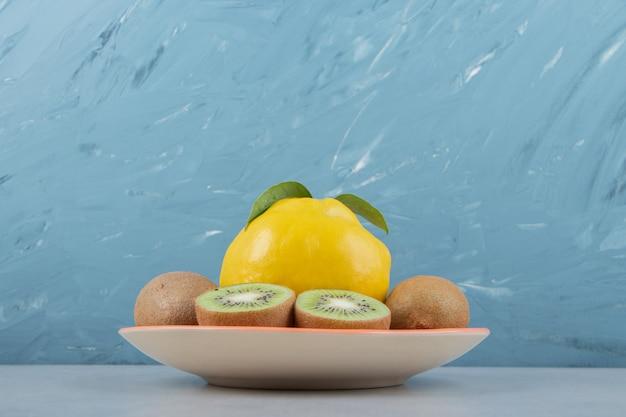 Coings et kiwis tranchés sur plaque orange.